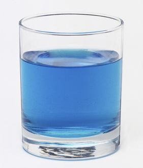 A glass filled with a blue liquid.