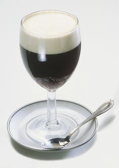 Glass of Irish coffee topped with cream, on saucer with teaspoon.