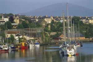 Great Britain, Wales, Caernarfon, quayside marina with town and mountain in background.