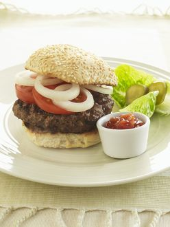 Hamburger stuffed with onions and tomatoes, served with salad garnish and bowl of