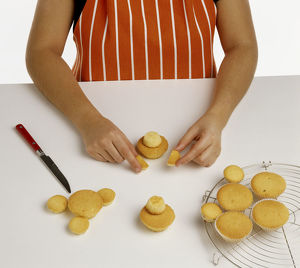 Hand model wearing an orange and white striped apron, making fairy fairy cakes using