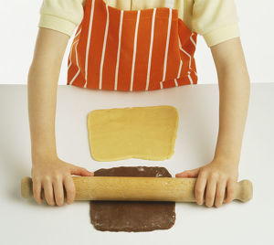 Hand model wearing orange and white striped apron, rolling out chocolate shortbread