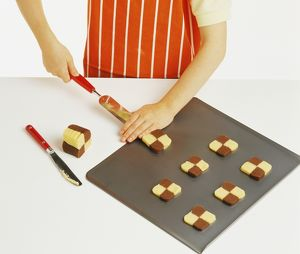 Hand model wearing orange and white striped apron, placing chocolate and plain shortbread