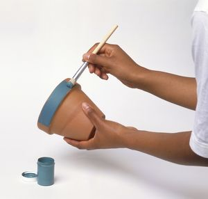 Hands painting a plant pot with blue paint