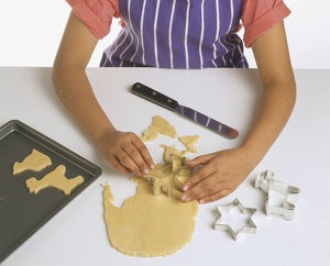 Hands of person cutting rolled cookie dough into shapes, high angle view