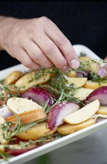 Hands sprinkling sprigs of fresh thyme over vegetables prepared for roasting