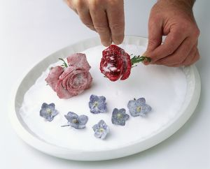 Hands sprinkling sugar over rose flower head, another rose flower head and African