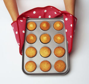 Hands wearing oven glove with fairy cakes in cake tin