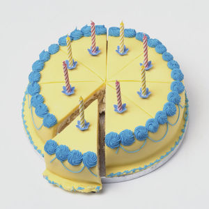 Iced birthday cake decorated with eight candles, one slice partially pulled out from centre