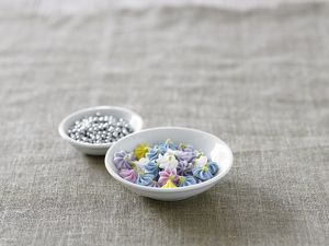 Icing sugar flowers and edible silver ball decorations