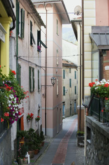 Italy, Genoa, Montebruno, narrow street lined with tall, pastel coloured buildings