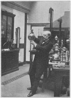 James Dewar (1842-1923) in his laboratory holding one of his vacuum flasks