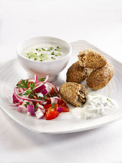 Kibbeh with salad and savoury sauce in plate, close-up