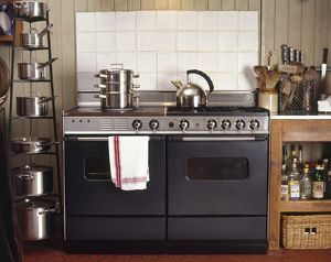Kitchen oven and hob unit with stainless steel kettle and steamer on top, pan shelving