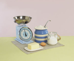 Kitchen scales, butter, egg, flour and sugar in containers on napkin on yellow tablecloth