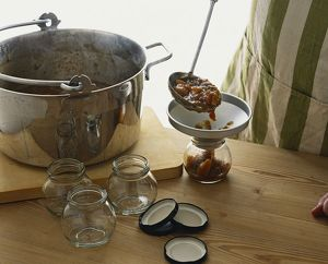 Ladling hot chutney into jar through funnel on wooden worktop