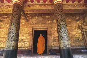 Laos, Luang-Phabang, Monk in doorway at Buddhist temple Wat Mai Suwannaphumaham