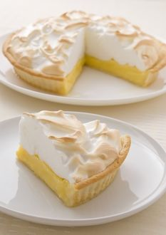 Lemon meringue pie on plate, single slice on plate in foreground, close-up
