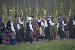 Lithuania, Klaipeda County, Curonian Spit, Nida, Torch lit procession of people wearing