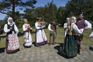 Lithuania, Klaipeda County, Curonian Spit, Nida, people wearing traditional costumes playing music