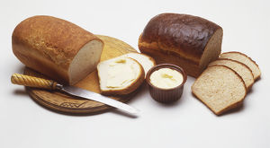 Loaves of white and brown bread, some slices cut away, a bowl of butter, a knife