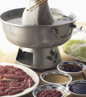 Mongolian hotpot, thinly sliced lamb, vegetables, and noodles in boiling water, served