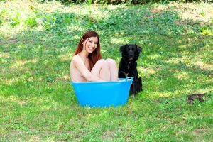 A Naked Woman Smiling in the Garden in a Bucket Blue with a Black Dog
