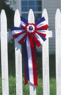 New England, Fourth of July red white and blue rosette on white picket fence, close-up