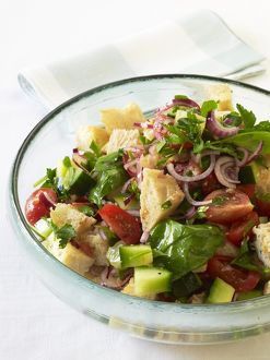 Panzanella, Italian bread salad containing mixed vegetables and herbs, served in glass bowl