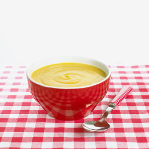 Pea soup in red bowl with spoon on red and white checked tablecloth, close-up