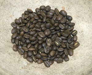 Pile of roasted coffee beans on stone surface
