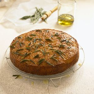Polenta cake and rosemary, with glass of olive oil, pastry brush and sprigs of rosemary