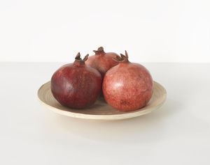 Three pomegranates on white plate