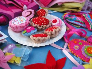 Pretend picnic with colourful cakes made from fabric at the centre, close-up