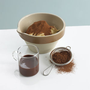 Pudding bowl with butter and cocoa powder next to glass of melted chocolate and sieve