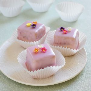 Raspberry cakes with pink icing and flower decorations on a plate, cake cases in