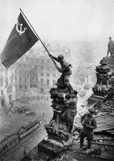 Red army soldiers raising the soviet flag over the reichstag in berlin, germany, april 30