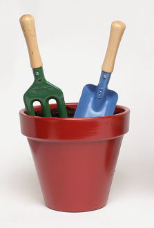 Red flowerpot with garden fork and trowel planted in it.