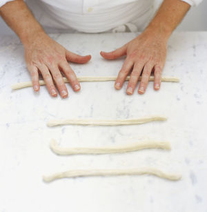 Rolling strips of dough back and forth on floured surface, high angle view