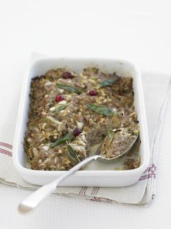 Sausagemeat stuffing, flavoured with sage and cranberries, in ovenproof dish, with spoon