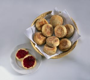 Scones in a basket, and sliced and topped with jam on a plate