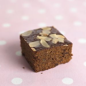 Slice of chocolate cake topped with walnuts on polka dot tablecloth, close-up