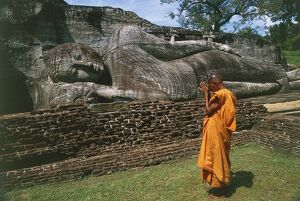 Sri Lanka, Ancient City of Polonnaruwa, Reclining Buddha statue and praying monk