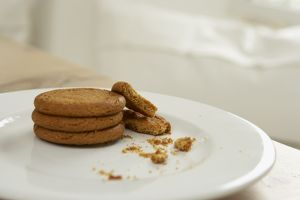 Stack and crumbs of ginger biscuits on white plate