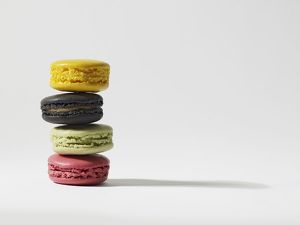 Stack of four yellow, brown, green and pink macaroons