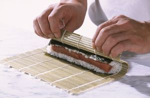 Sushi containing nori seaweed, rice and tuna, being hand-rolled inside bamboo mat