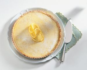 Tarte au Citron topped with lemon twists and icing sugar, served on white plate, with napkin