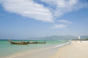 Thailand, Phuket, Ao Karon, beach at tourist resort with traditional boats moored