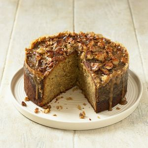 Toffee banana cake topped with nuts, sliced