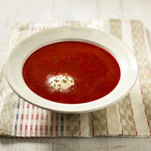 Tomato borscht served in soup bowl with sour cream and cumin seeds